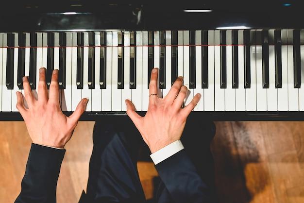 Pianist die een stuk op een grote piano met witte en zwarte sleutels uitvoert. Premium Foto