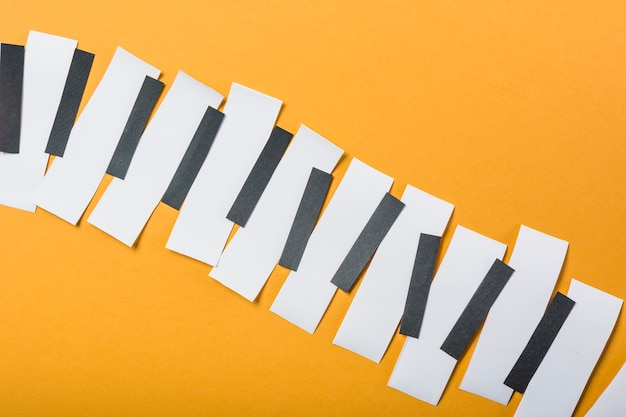 Pianotoetsen gemaakt met zwart-wit papier op gele achtergrond Gratis Foto