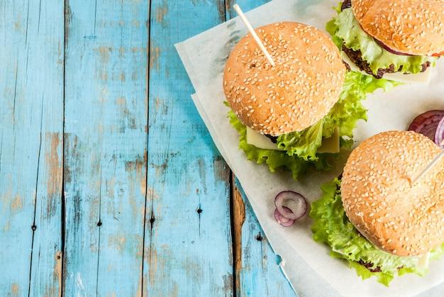 Picknick fastfood ongezond eten heerlijke verse smakelijke hamburgers met rundvlees kotelet verse groenten en kaas op oude rustieke blauwe houten tafel met frisdrank water Premium Foto
