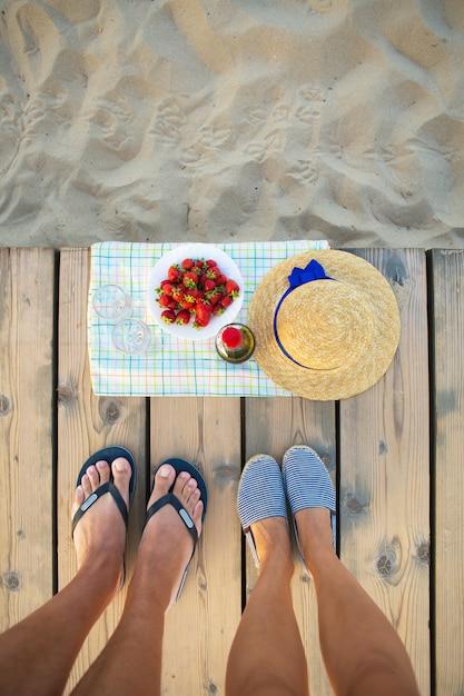 Picknick in de buurt van de zee-hoed, wijn, glazen, aardbei Premium Foto