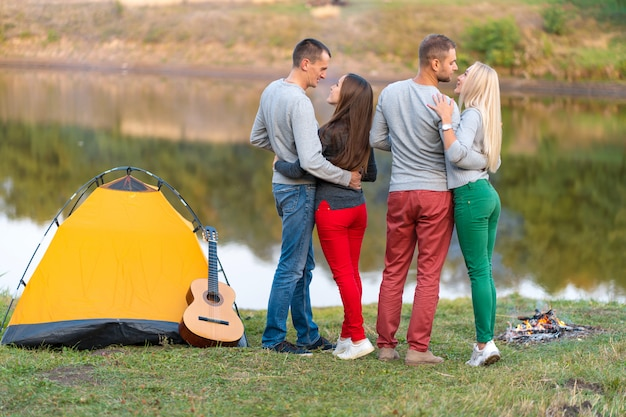 Picknick met vrienden binnen bij meer dichtbij het kamperen tent. bedrijfvrienden die de aardachtergrond van de stijgingspicknick hebben. wandelaars ontspannen tijdens het drinken. zomerpicknick. leuke tijd met vrienden. Premium Foto