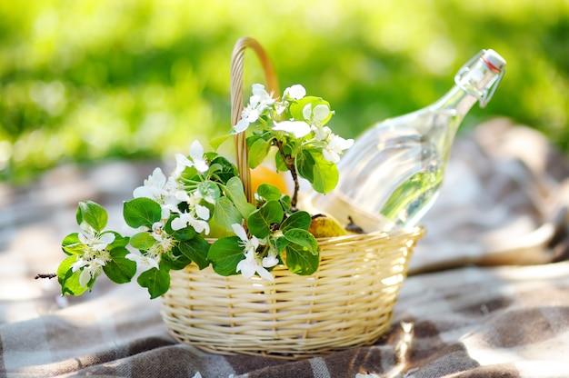 Picknickmand met fruit, bloemen en water in de glazen fles Premium Foto