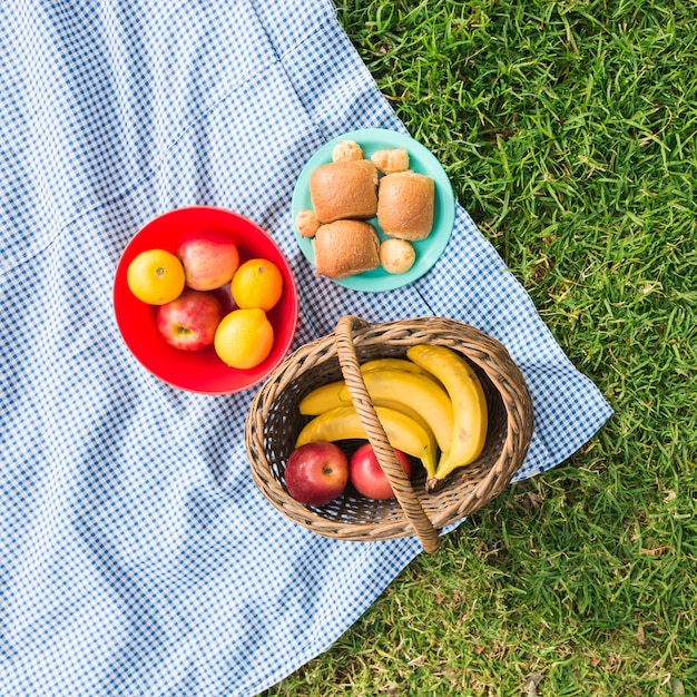 Picknickmand met fruit en brood op controledeken over groen gras Gratis Foto