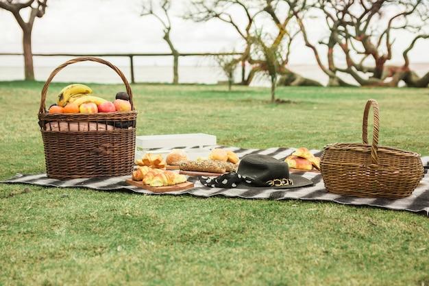 Picknickmand met gebakken brood en hoed op deken Gratis Foto