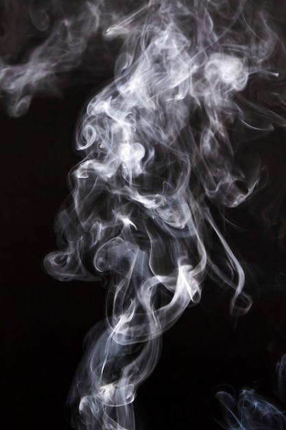 Piekerige rookwolken die op zwarte achtergrond worden uitgespreid Gratis Foto
