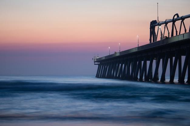Pier in de buurt van de kalme zee onder de prachtige avondrood Gratis Foto