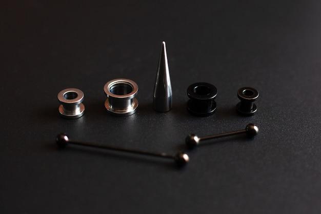 Piercingaccessoires op zwarte close-up roestvrijstalen sieraden voor lekke liefhebbers Premium Foto