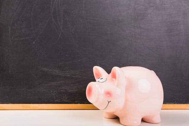 Piggy bank geplaatst op schoolbord Gratis Foto