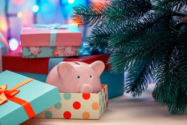 Piggy bank onder een kerstboom in een vakantiedoos Premium Foto
