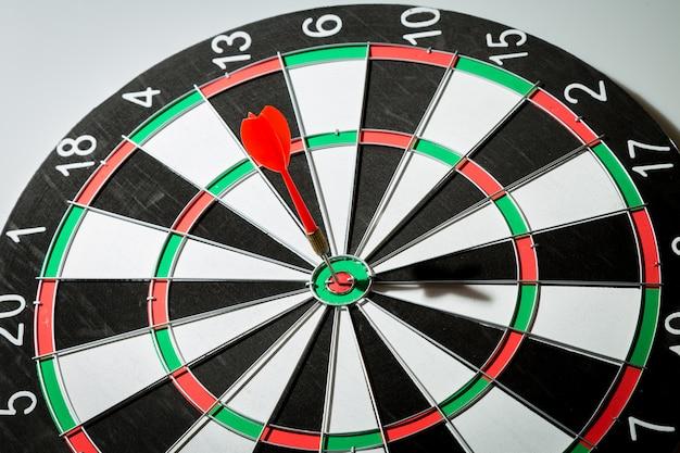 Pijltjepijl die in het doelcentrum van dartboard raakt. concept van het succes Premium Foto