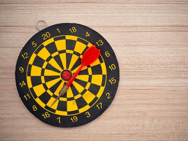 Pijltjepijl en dartboard op bruine houten achtergrond Premium Foto
