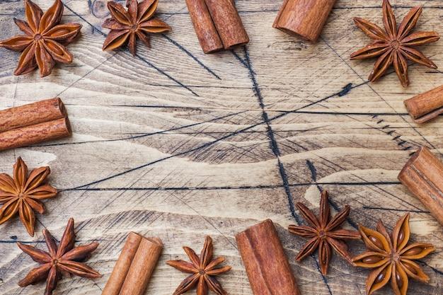 Pijpjes kaneel en anijsplantsterren op houten achtergrond. Premium Foto