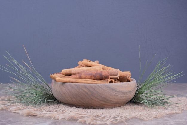 Pijpjes kaneel in een houten kop met rond eikenboomtak Gratis Foto
