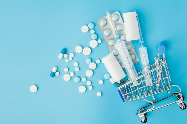 Pillen en medische injectie in het winkelen karretje op blauwe achtergrond. creatief idee voor zorgkosten, drogisterij, ziektekostenverzekering en farmaceutisch bedrijf bedrijfsconcept. kopieer ruimte. Premium Foto