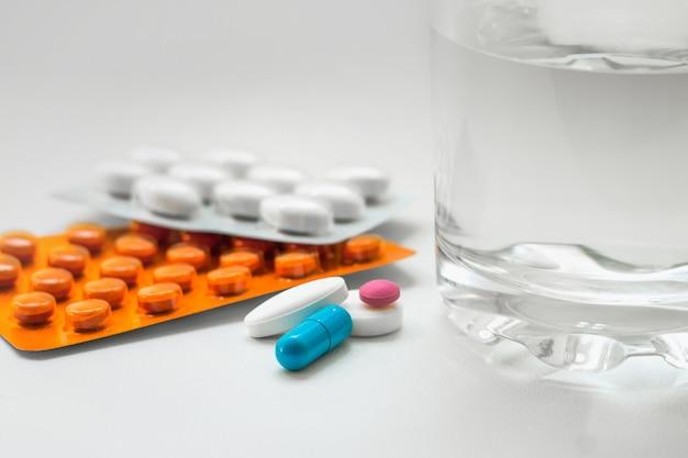 Pillen in een blister, capsules, een glas water op een witte achtergrond. preparaten voor de behandeling van verkoudheid, vitamines, wellnesscomplex Premium Foto