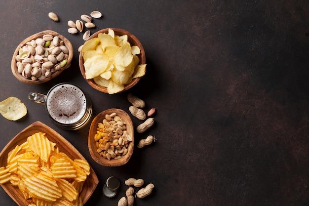 Pils en snacks op stenen tafel Premium Foto