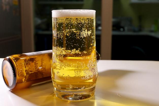Pils met schuim in het glas op witte houten van tegenbar met bierfles. Premium Foto