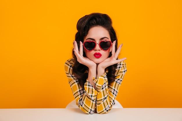 Pinup meisje poseren in hartvormige bril. mooie vrouw met lichte make-up zittend op gele achtergrond. Gratis Foto