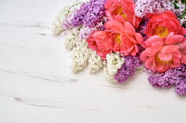 Pioenrozen en lila bloemen op witte houten achtergrond. Premium Foto