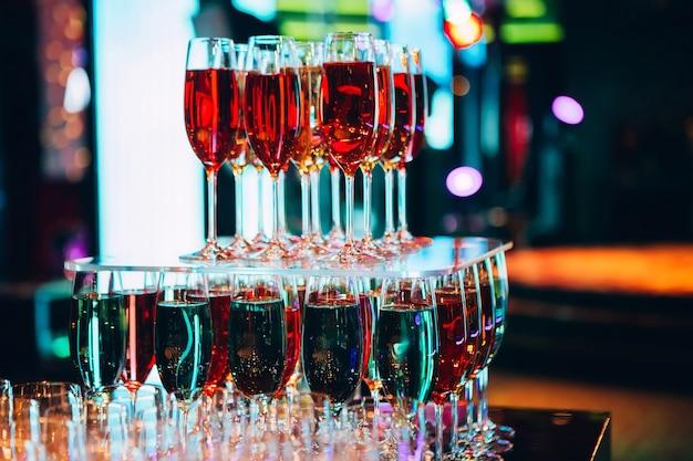 Piramide van champagneglazen. veel glazen champagne op de bar. bubbels champagne in een glas. gekleurde champagne. Premium Foto