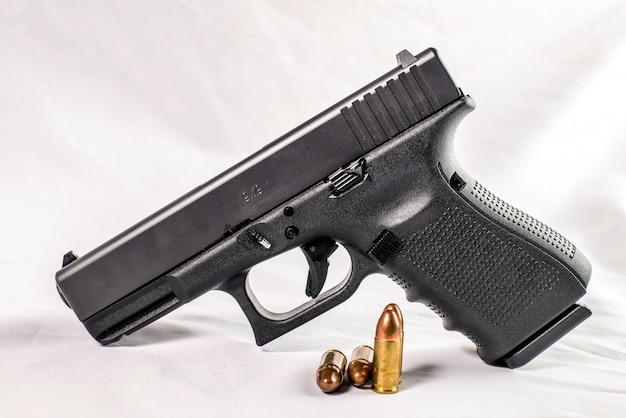 Pistoolkanon en kogels van 9 mm die met munitie op houten achtergrond zijn uitgestrooid Premium Foto