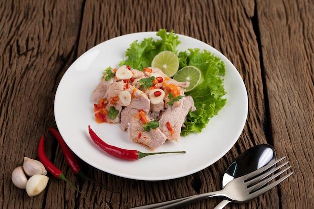 Pittig limoenvarkensvlees met laos, laos, chili, tomaat en knoflook op een witte plaat op een houten vloer. Gratis Foto