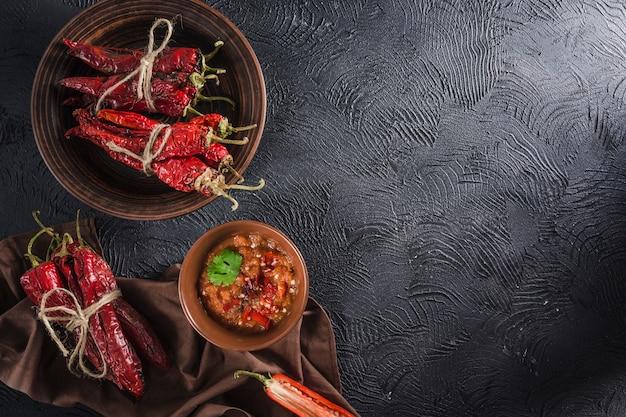 Pittige chili op een donkere achtergrond in keramische platen Premium Foto