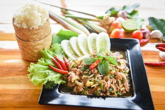 Pittige fijngehakte varkensvleessalade thais eten met kruiden en specerijen ingrediënten kleefrijst traditie noordoosten eten isaan. Premium Foto