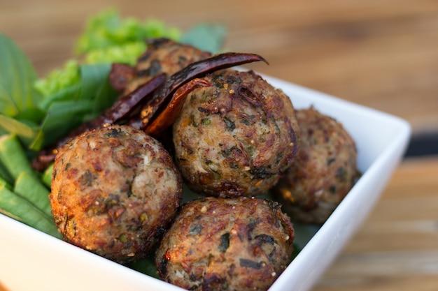 Pittige gehakt varkensvlees ballen met salade in een witte plaat op de tafel. thais eten (larb moo tod) Premium Foto