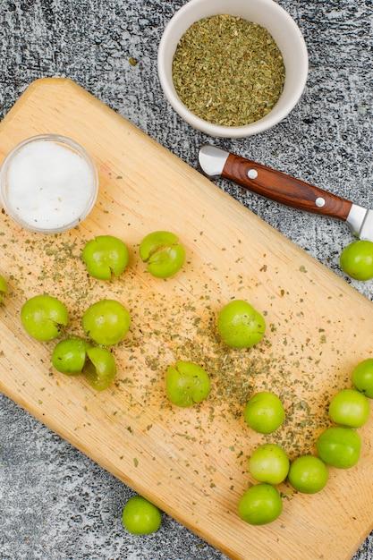 Pittige groene pruimen met een kleine reep zout, gedroogde tijm en een fruitmes in een snijplank op grijze grunge oppervlak, close-up. Gratis Foto