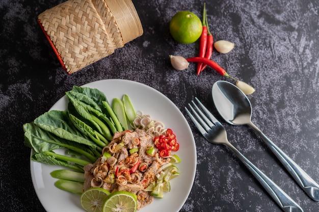 Pittige limoensalade met boerenkool, laos, spaanse peper en knoflook in een witte plaat op een zwarte cementvloer. Gratis Foto