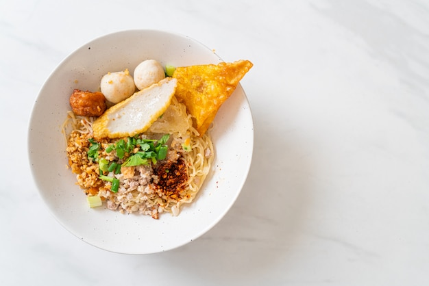 Pittige noedels met visballetje en varkensgehakt (tom yum noodles) Premium Foto