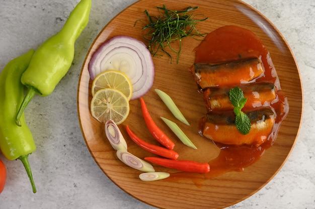 Pittige salade van sardine in tomatensaus op houten dienblad Gratis Foto