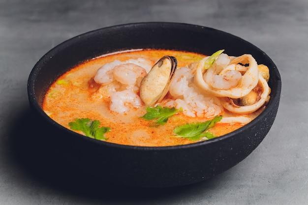 Pittige thaise soep tom yam met kokosmelk, spaanse peper en zeevruchten garnalen en zalm in een plaat op een zwarte achtergrond. aziatische keuken, restaurantmenu. Premium Foto