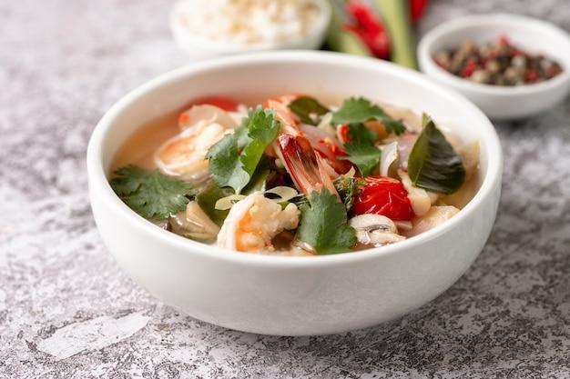 Pittige tom yam kung, tom yum zure soep met garnalen, garnalen, kokosmelk, citroengras en chilipeper in een kom Premium Foto