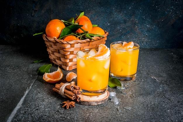 Pittige winter mandarijn cocktail met wodka, verse mandarijnen, kaneel en anijs, op donkere achtergrond, kopie ruimte Premium Foto