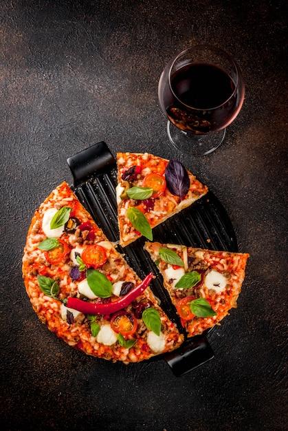 Pizza en rode wijn op donkere achtergrond Premium Foto