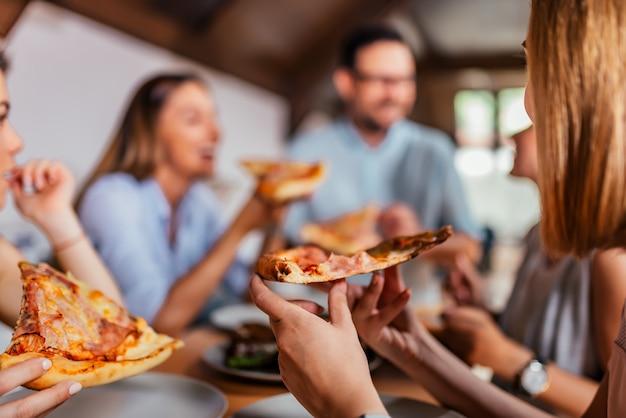 Pizza eten met vrienden. detailopname. Premium Foto