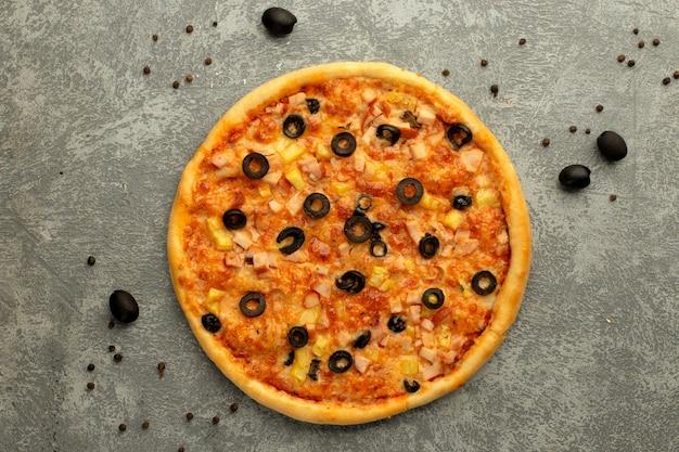 Pizza gegarneerd met gesneden olijf Gratis Foto