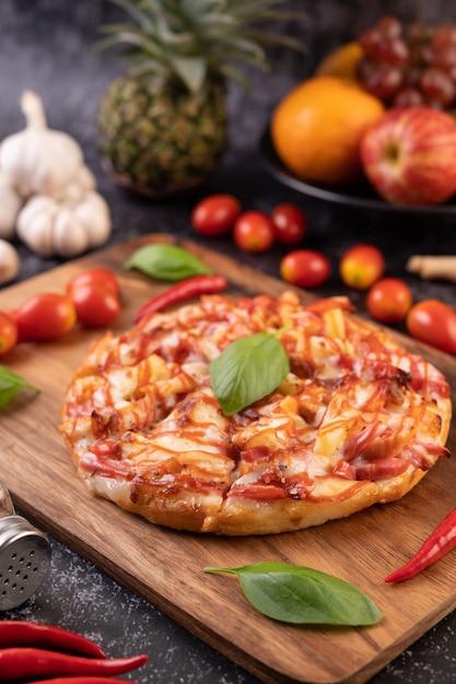 Pizza in een houten bakje met tomaten chili en basilicum. Gratis Foto