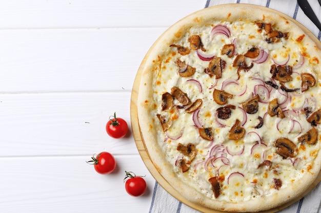 Pizza met champignons en ui aan boord op witte houten tafel close-up Premium Foto
