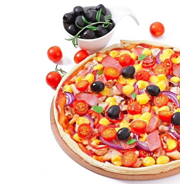Pizza met groenten, kip, ham en olijven geïsoleerd op wit Gratis Foto
