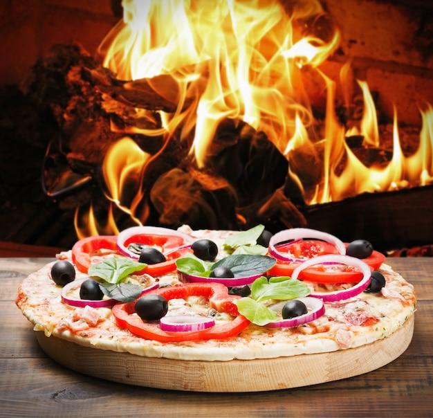 Pizza met ham en kaas gekookt op het vuur Premium Foto