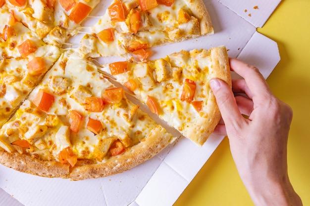 Pizza met kip en tomaten in een doos. hand haalt een plak pizza. Premium Foto