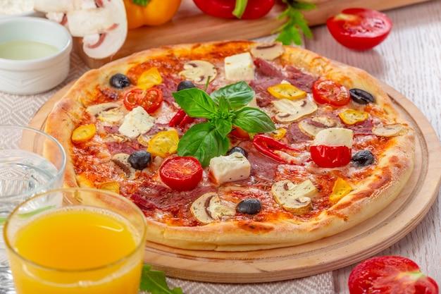 Pizza met mozzarella, ham, cherry tomaten, zwarte olijven Premium Foto