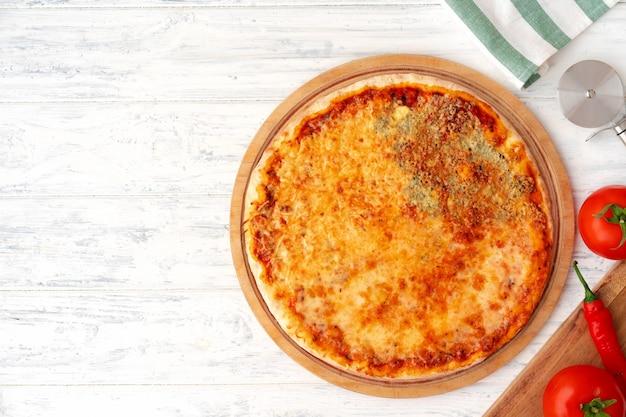 Pizza met vier kazen geserveerd op houten achtergrond bovenaanzicht Premium Foto