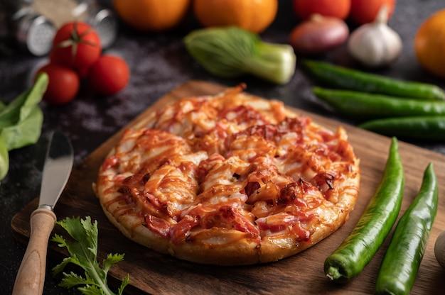 Pizza met worst, maïs, bonen, garnalen en spek op een houten plaat Gratis Foto