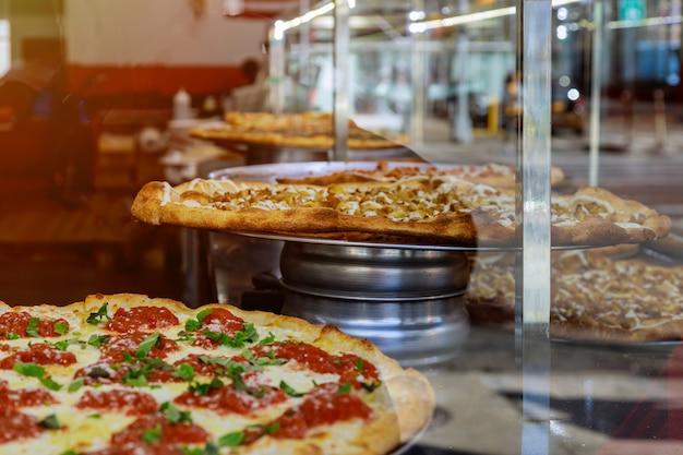 Pizza op een houten aanrecht van groot deel van de stijl van pizza new york Premium Foto