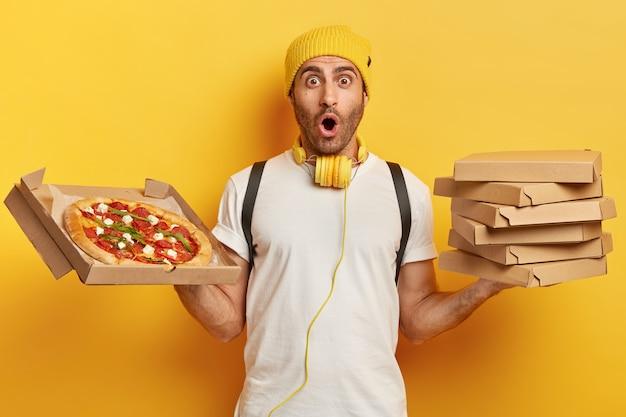 Pizzadealer houdt kartonnen dozen met snack vast, kijkt met omg-uitdrukking, draagt gele hoed en wit t-shirt, onder de indruk van iets, heeft veel werk Gratis Foto