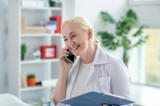 Pjhone-oproep. blonde arts glimlachend en praten aan de telefoon Premium Foto